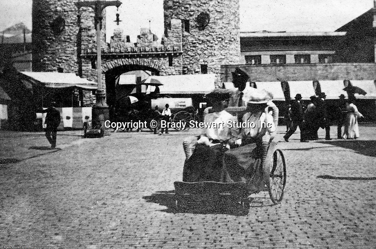 St Louis MO:  View of a carriage used to transport people around the park at the Louisiana Purchase Exposition.  The view included the Country of Ireland's exhibit on the pike
