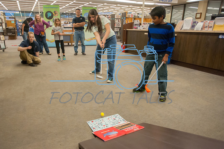 Katie Tubiello attempts a difficult ramp shot while other watch during the Mini Golf Night at the Carson City Library on May 9, 2014. Parents and children enjoyed turning the library into a mini golf course. The kids used engineering concepts to build ramps, tunnels and obstructions.<br />