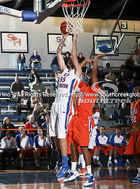 Texas-Arlington Mavericks forward Jordan Reves (55) goes in for a layup over Houston Baptist Huskies forward Terry Bembry (24) in the game between the UTA Mavericks and the Houston Baptist Huskies held at the University of Texas in Arlington's Texas Hall in Arlington, Texas. UTA defeats Houston Baptist 72 to 57
