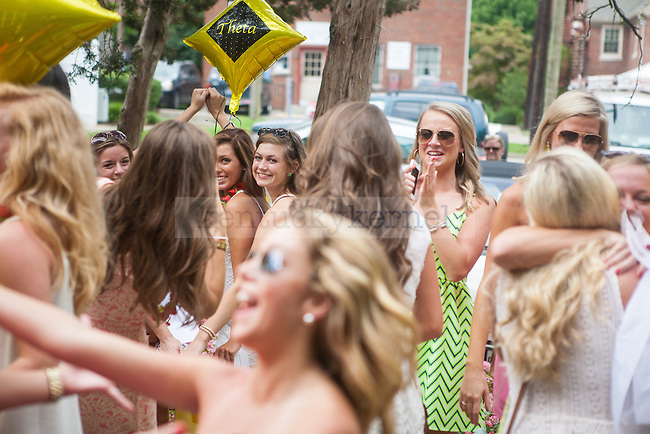 A group of Kappa Alpha Theta sisters pose for a photo in the background while others celebrate during UK's sorority bid day in Lexington, Ky., on Friday, August 22, 2014. Photo by Adam Pennavaria | Staff
