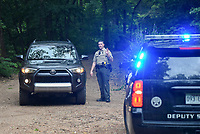NWA Democrat-Gazette/CHARLIE KAIJO A Benton County Sheriff's Deputy directs traffic, Friday, July 5, 2019 on the intersection of Crossover Rd and Gorden Hollow Rd in Gravette. <br /> <br /> Police responded to a shooting situation that left four people dead in an apparent murder suicide on a nearby property. All four people are related or lived at the residence. One body was found on the driveway. Authorities do not believe there is a danger to the public.