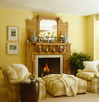 A pair of club chairs and an ottoman upholstered in large check infront of the pine-clad fireplace in the family room