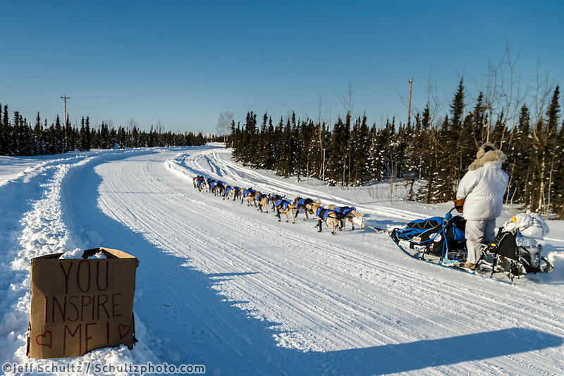 Tim Hunt runs down the road past one of several welcome signs on his way into the Huslia checkpoint on Saturday  March 14, 2015 during Iditarod 2015.  <br /> <br /> (C) Jeff Schultz/SchultzPhoto.com - ALL RIGHTS RESERVED<br />  DUPLICATION  PROHIBITED  WITHOUT  PERMISSION
