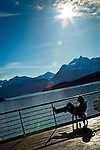 Alaska Marine Highway System sailing through Lynn Canal, Inside Passage, SE Alaska on a sunny afternoon.  Snow capped mountains are towering over the ocean. A silhouette of man reading a book on a deck chair.
