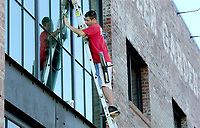NWA Democrat-Gazette/DAVID GOTTSCHALK  Stephen Medley, window cleaning technician with Fish Window Cleaning of Springdale, cleans Monday, October 10, 2017, windows on the north side of JJ's Beer Garden and Brewing Company, JBGB, in Fayetteville. Medley was working with John Wright, operations and sales,  and Bill Welsh, owner of the service that specializes in both commercial and residential window cleaning.