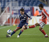 Jay Heaps (Revolution, blue) passes as Paulo Nagamura (Toronto, red) defends. New England Revolution defeated Toronto FC, 4-0, at Gillette Stadium in Foxborough MA on April 14, 2007. The 4th goal was the Revolution team's 500th goal.