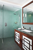 Small glass wall tiles add a reflective turquoise hue to this ensuite bathroom