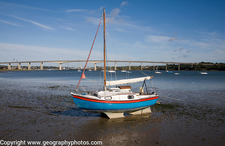 Sailing boat in mud at low tide with the Orwell Bridge in the background, River Orwell estuary, Freston Point, Suffolk, England