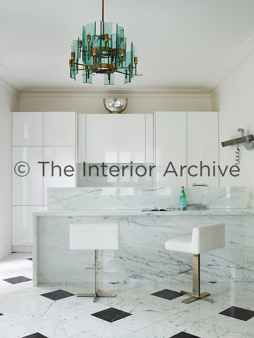 The luxury kitchen has bespoke cabinetry and an impressive Nero Marquina marble island. The simple 1970s barstools and the 1950s FontanaArte chandelier complete the sleek, minimal feel.