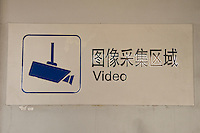 Daytime landscape view of video security monitoring signage on a wall at a B?ij?ng dìti?zhàn in D?ngchéng Q? in Beijing.  © LAN