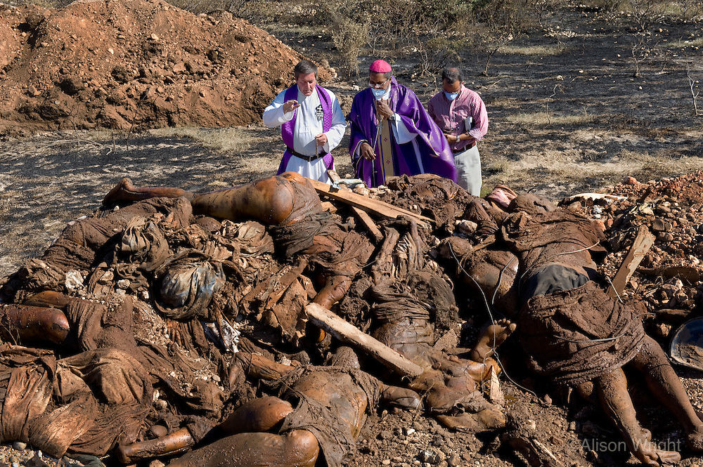 Devastation after the January 12, 2010 earthquake. Father Rick and Bishop Pierre Dumas perform blessings over mass graves in Titanyen. The state left the bodies piled up and they brought in bulldozers to give them a proper burial.