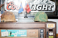 Helmets and military flags stand on a cigarette vending machine in front of a Coors Light mirror sign while Ohio governor and Republican presidential candidate John Kasich speaks at a town hall campaign event at Raymond VFW Post 4479 in Raymond, New Hampshire, on Wed., Feb. 3, 2016.