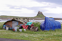 Recyled boat beside Clinker hull with Holy Island Castle as backdrop