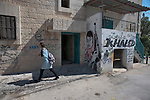 A school girl walks in the Palestinian refugee camp of Aida, in Bethlehem, West Bank, next to a graffiti of Leila Khaled.<br />
