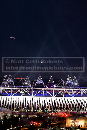 27/07/2012. LONDON, UK. Two parachutists, one dressed as the Queen, the other as James Bond, are seen over the Olympic Stadium after dropping from a helicopter during the opening ceremony of the 2012 Summer Olympics in London today (27/07/12). Constituting the third time the Olympic Games have been held in Great Britain, the 2012 Olympic Games, also known as the Games of the XXX Olympiad opened this evening with a show, put together by 'Slum Dog Millionaire' director Danny Boyle, entitled 'The Isles of Wonder. Photo credit: Matt Cetti-Roberts