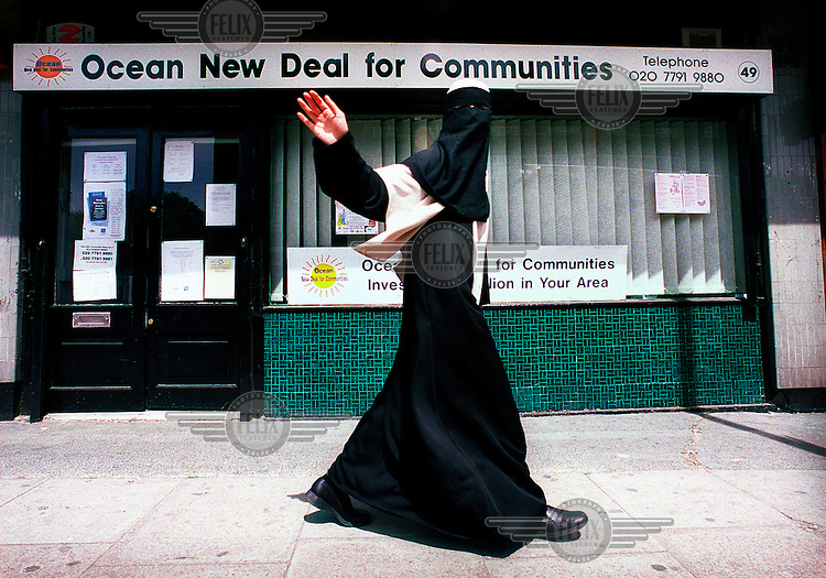 A Muslim woman wearing a niqab veil passes a community centre in Tower Hamlets.