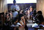 Ipixuna Village, Brazil. Arawete amerindian children in the village school learning Portuguese with teacher. Para State.