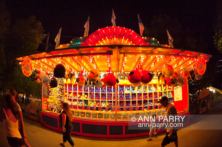 Aug. 25, 2012 - Middlebury, Connecticut, U.S. - The Water Gun Fun game booth displays stuffed animal prizes and has colorful lights at night, as people pass by, at Quassy Amusement Park. View taken with 180 degree fisheye lens.