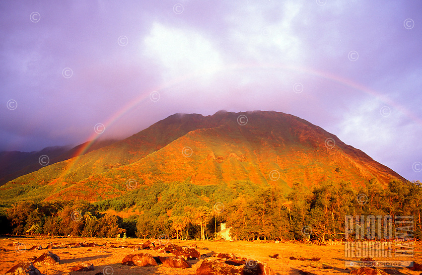 Rainbow over the Kalawao district, on the Kalaupapa peninsula, with St. Philomena Church in the background