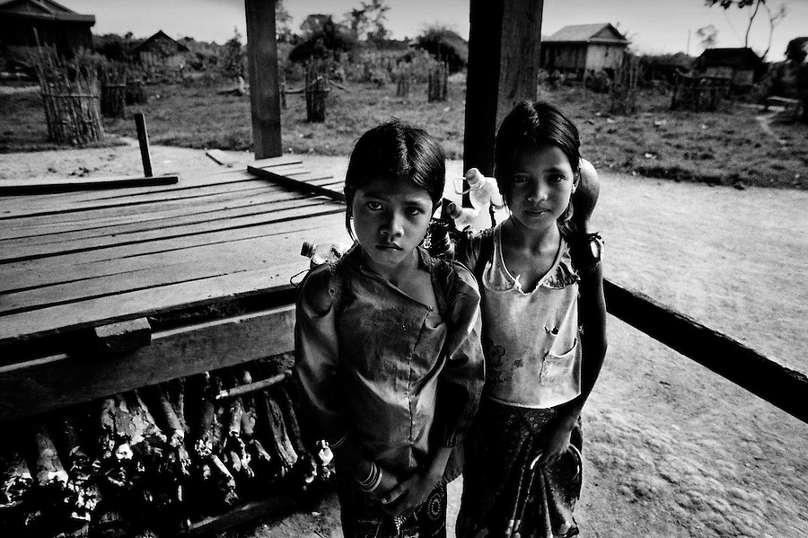 """Mekong Dam Victims - Cambodia. Two girls carrying baskets with empty bottles on their way to the river to collect water. The people still use the water from the river for domestic use, despite the bad water-quality after the construction of dams up-river. At least 55.000 people living near the Sesan river in Cambodia's Ratanakiri and Stung Treng provinces continue to suffer due to lost rice production, lost fishing income, drowned livestock and damaged vegetable gardens, and so also great economical losses, because of the unpredictable floodings from the Yali Falls Dam on the other side of the border in Vietnam. To this day, flash floodings have caused the deaths of at least 39 villagers from various ethnic minority groups living along the river. Despite this, four other major hydropower projects are now in operation or under construction on the Sesan River in Vietnam. Known as """"The Mother of Waters"""", more than 60 million people depend on the Mekong river and its tributaries for food, fresh water, transport and other aspects of daily life. The construction of big dams is now threatening the life of these people aswell as the vital and unique ecosystem of the river."""