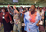 Participants, including Andris Salter (right) and Marilyn Reid, both staff of United Methodist Women, sing during an April 27, 2014, worship service at the United Methodist Women's Assembly in Louisville, Kentucky.
