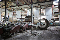 India – West Bengal: The abandoned processing factory at Bundapani Tea Estate, in the Dooars region. The garden, which houses more than 7,000 people, used to employ around 1,215 workers until it closed down in July 2013. In the hope the garden will reopen again one day, voluntary caretakers patrol the factory to prevent ransackers from looting machinery and equipments.