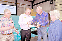 RACHEL DICKERSON/MCDONALD COUNTY PRESS Jim Armstrong, left, and Michael Griffith of Cornerstone Bank present Jim and Naomi Cooper of Cooper Gear with a trophy recognizing their 25 years in business during a celebration on June 13.
