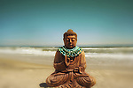 A buddha on a sandy beach