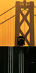 The California Street cable climbs up to Nob Hill where the Bay Bridge tower is illuminated by the morning sun in San Francisco, California.  .