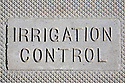 """Irrigation Control"" sign on cement cover to irrigation system for commercial landscape watering."