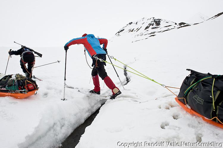 Dame med pulk krysser smeltevannsbekk. ---- Woman pulling sled across melt water stream.