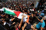 Mourners carry the body of 14-year-old Palestinian boy Yasser Abu Al-Naja, who was killed by Israeli troops during clashes in tents protest where Palestinian demand the right to return to their homeland at the Israel-Gaza border, during his funeral in Khan Younis, in the southern Gaza Strip June 30, 2018. Photo by Ashraf Amra