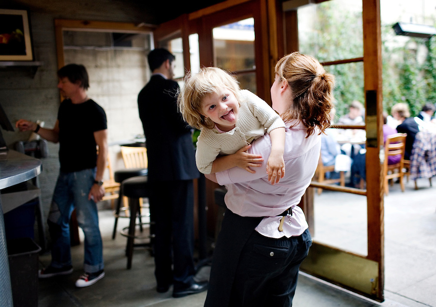 Server Aimee Rogers, plays with Pearl Pirie-Clark, 3, daughter of restaurant chefs and owners, Gayle Pirie and John Clark, in the early part of the evening, at Foreign Cinema, in San Francisco, CA., on Friday, June 12, 2009..