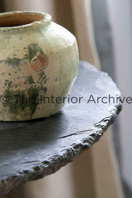A green-glazed terracotta Han jar on a rough-hewn slate table in the living room