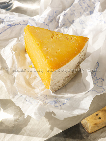A wedge of artisanal cheese on its paper wrapper, lit as a bright sunny day