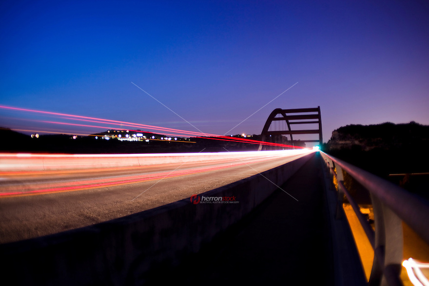 Cars and trucks jettison through the 360 Bridge as if it were a time machine on the Capital of Texas Highway and Lake Austin