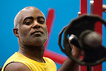 African American man lifting weights in gym