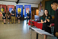 NWA Democrat-Gazette/CHARLIE KAIJO Head of School, John Rocha (right), hands a mic over to 9th grader Mary Helen Schaefer during an open house, Sunday, March 4, 2018 at Ozark Catholic Academy in Tontitown. She will be part of the school's inaugural class<br /><br />Ozark Catholic Academy, which is gearing up to open this fall, celebrated a milestone as they announced their mascot.