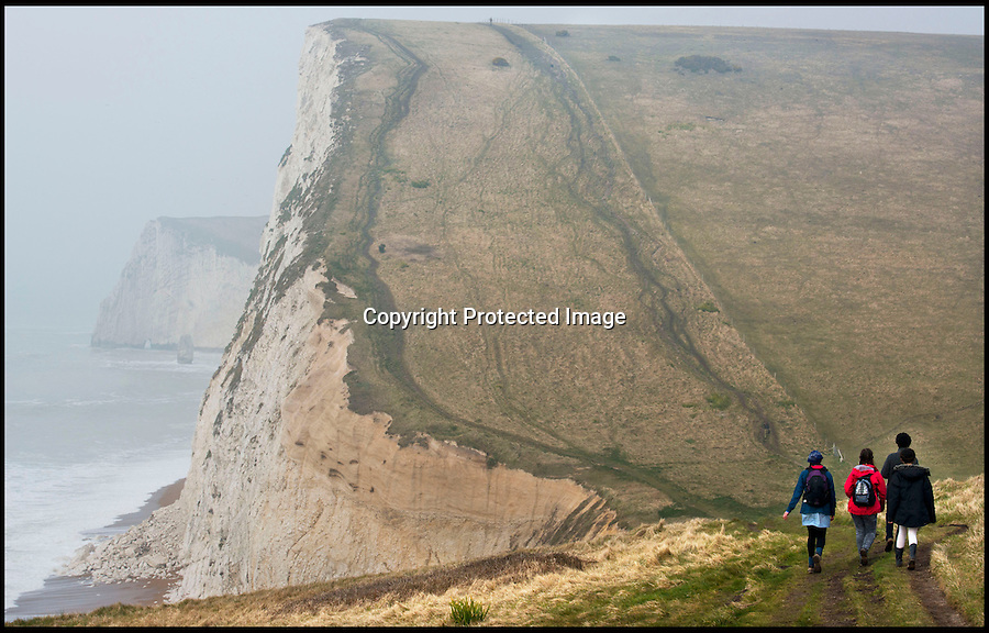 BNPS.co.uk (01202 558833).Pic: RachelAdams/BNPS..Walkers on the spectacular South West Cliff path...Unprecedented weather takes its toll on Britains crumbling coast...The South West coast path is under threat after a series of landslips and cliff falls have left the Jurassic coast World Heritage site with some dinosaur sized clefts and chasm's...Walkers could soon face being deprived of some of the country's most beautiful views after the prolonged cold and wet winter has led to a series of devastating landslides...Since last April heavy rain has caused several landslides on large sections of the Jurassic Coast in Dorset, forcing authorities to close parts of the popular coastal path...Last July holidaymaker Charlotte Blackman, 22, was killed when a landslide caused 400 tons of rocks to fall on her from above as she walked along a beach at Burton Bradstock...And a recent landslide at popular tourist spot Durdle Door means sections of the nearby coastal path overlooking the famous sight have been closed due to safety concerns...On that occasion around 400 tons of chalk rock covered the beach below after collapsing from the 90-million-years-old cliff...Fresh cliff falls and cracks appeared along the coast on Sunday as coastguards issued a warning saying the pathway is falling away.