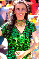 Belly dancer dressed in green shimmering gear. In the Heart of the Beast May Day Festival and Parade Minneapolis Minnesota USA