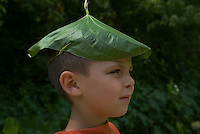 Young boy in orange shirt wears green pond lily pad frond as hat in sunlight