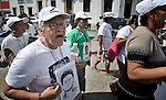 Santos del Socorro Rojas holds a photo of her son Jorge Alberto Reyes D&aacute;vila as she walks with a group of Central Americans during a demonstration in the center of Tapachula, Mexico, on December 16, 2013. The group, mostly mothers looking for their children, spent 17 days touring 14 Mexican states in search of their loved ones, most of whom had disappeared while following the migrant trail north. They also demanded that Mexican government officials improve their treatment of migrants transiting the country.<br /> <br /> Rojas, from Chinandega, Nicaragua, was reunited with her son later that same day after people at a church-run migrant shelter recognized the photo. They had been separated for nine years.