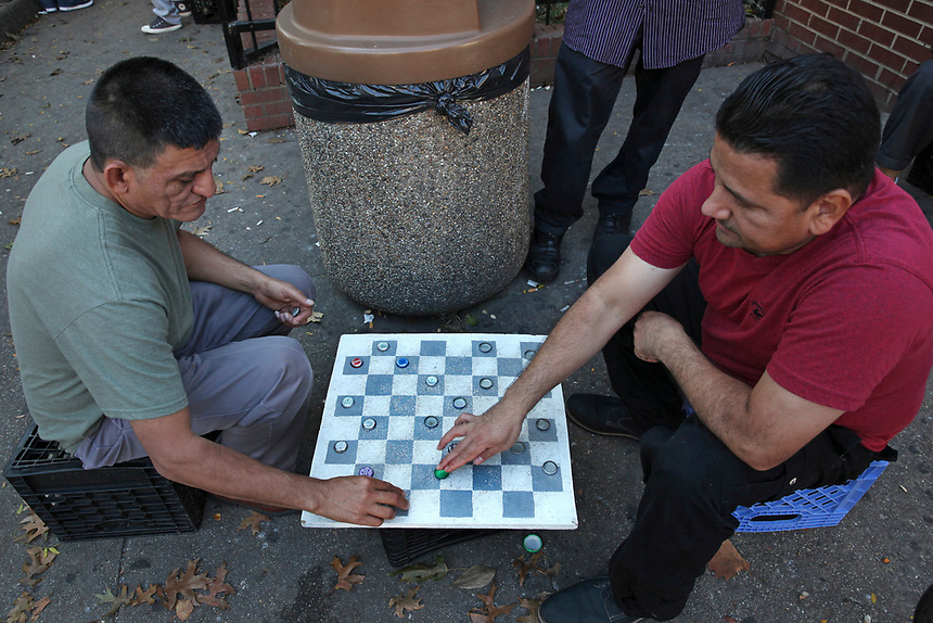 (171015RREI5529)  La Esquina where Latinos have gathered for decades at the corner of Mt. Pleasant St. and Kenyon St. NW. to play chekers (damas). Jorge (lgreen shirt). Washington DC Oct. 15 ,2017 . ©  Rick Reinhard  2017     email   rick@rickreinhard.com