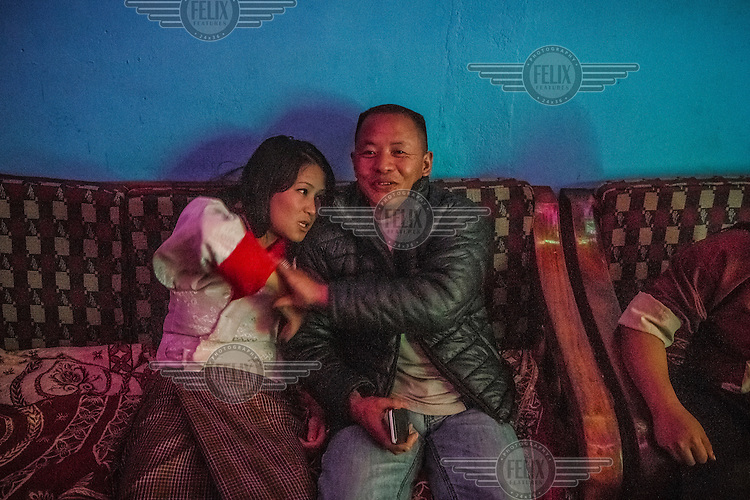A drunk customer of 'Tashi Tagay drayang' grabs a female dancer who works at the club. Drayangs are clubs where girls work dancing for male clients. Most of the girls come from poor rural families and for them it's an easy way to earn some money. They wear traditional Bhutanese clothes and dance for men who come to the 'drayangs' to drink beer. Although officially all 'drayangs' close their doors around midnight and girls are supposed to sleep inside, many clients exchange their phone numbers with the dancers and later meet somewhere else for sex.