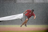 Greg Burgess, head of operations and grounds at the Greenville Drive, pulls the tarp during a sudden downpour at Game 2 of a doubleheader against the Rome Braves on Friday, August 3, 2018, at Fluor Field at the West End in Greenville, South Carolina. (Tom Priddy/Four Seam Images)