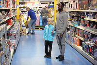 Pictured: Nathan Dyer helps a young boy find a toy Wednesday 08 December 2016<br />Re: Swansea City FC players have bought Christmas gifts for 60 children at Smyths toy store in Swansea, south Wales.