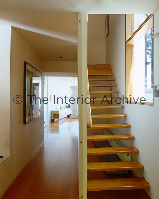 An open staircase with wooden treads leads up from a narrow hallway