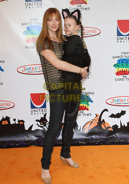 JUDY GREER & guest.18th Annual Camp Ronald McDonald For Good Times Halloween Carnival held at Universal Studios Back Lot, Universal City, CA, USA..October 24th, 2010.full length top jeans denim black lace beige carrying cat costume kid child .CAP/ADM/KB.©Kevan Brooks/AdMedia/Capital Pictures.