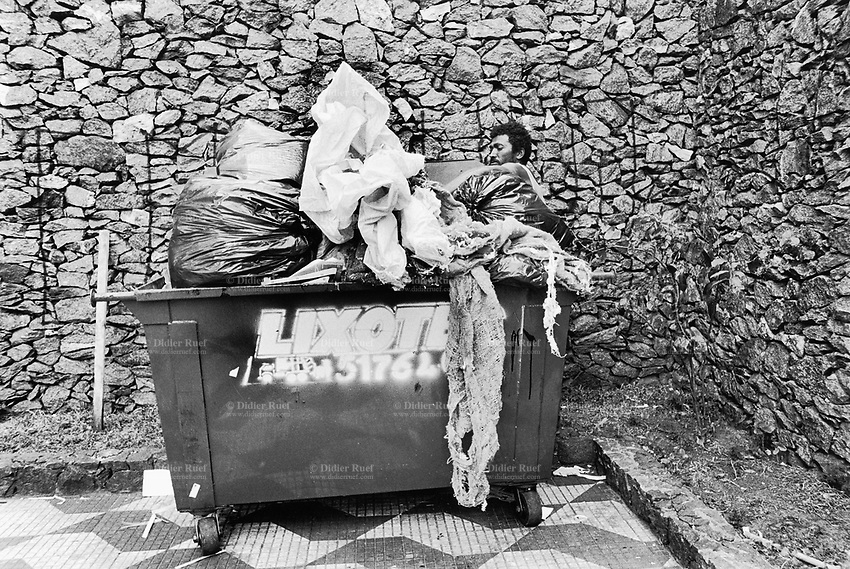 "Brazil. Sao Paulo state. Sao Paulo. Valdemir is a poor man who lives in the street. He is checking the contents of a bin full of garbage. The ""catadores"" are men who collect paper, plastics, metals, bottles ... in order to sell these items as recycled materials and make a living. Waste collector. Stones wall.  © 1994 Didier Ruef .."