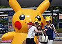 """August 10, 2016, Yokohama, Japan - People take souvenir photos with dozens of Pikachu balloons, Nintendo's videogame software Pokemon's wellknown character, at a station suare in Yokohama, suburban Tokyo on Wednesday, August 10, 2016. The Pikachu mascots walk around the shoppjng mall daily to attract summer vacationers as a part of the """"Great Pikachu Outbreak"""" event through August 14.    (Photo by Yoshio Tsunoda/AFLO) LWX -ytd-"""